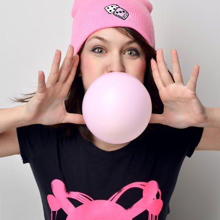 Close up funny fashion portrait of cheerful woman inflating the bubble gum in hot pink party hat on a background