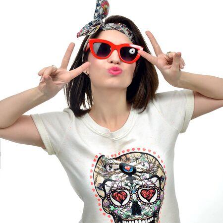 Mujer Morena atractiva en gafas de sol rojas que muestran signo de la paz por las manos sobre un fondo blanco