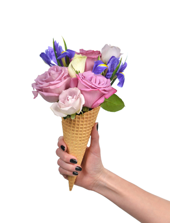 Woman hand holding roses and iris flowers in waffle cones close up isolated on a white background