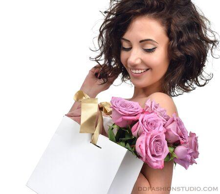 mujer con rosas: Bastante joven morena con franjas de oro bolsa de compras y rosas flores de color púrpura de la mujer aislada sobre un fondo blanco Foto de archivo
