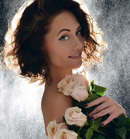 wild hair: Beautiful curly hair woman with bouquet of wild roses flowers with green leafs on black background