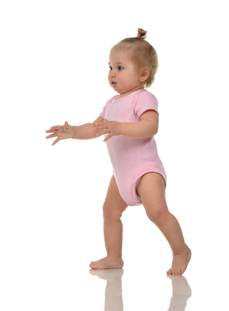 young girl barefoot: Infant child baby girl kid toddler in pink body cloth make first steps isolated on a white background