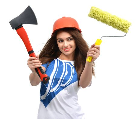 architect tools: Young beautiful woman in orange construction safety hat show axe and yellow paint brush  isolated on white background