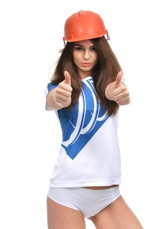 Young strong beautiful woman showing thumbs up smiling laughing looking at camera in orange construction hat isolated on white background Stock Photo