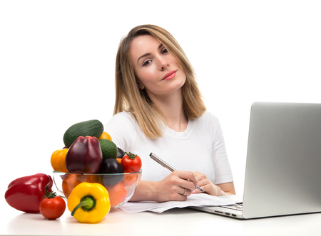 dietology: Confident nutritionist woman working at desk with fresh fruits and vegetables and modern laptop computer isolated on a white background