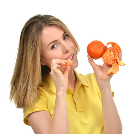 Woman eating tangerine mandarin fruit isolated on white background. Diet nutrition healthy lifestyle concept Stock Photo