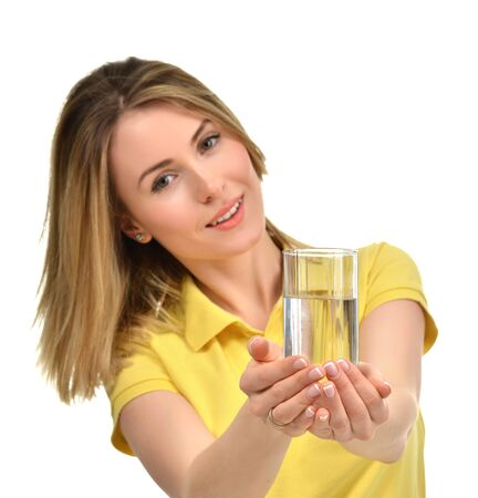 tomando agua: Beautiful healthy woman give drinking water glass in yellow polo isolated against white background Foto de archivo