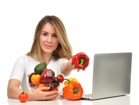 dietology: Confident nutritionist woman working at desk with modern laptop computer near fresh fruits and vegetables and showing red paprika pepper isolated on a white background
