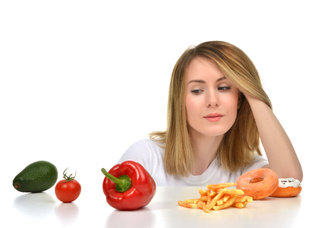 unhealthy diet: Dietician woman looking at vegetables avocado tomato pepper and fast food french fries and sweet unhealthy donuts isolated on white background. Diet nutrition healthy lifestyle concept.