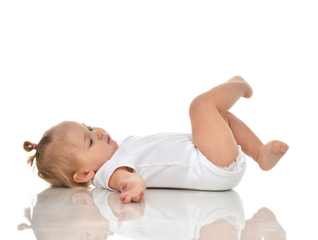 white back: Funny Infant child baby girl in diaper lying on a back and looking on her legs isolated on a white background