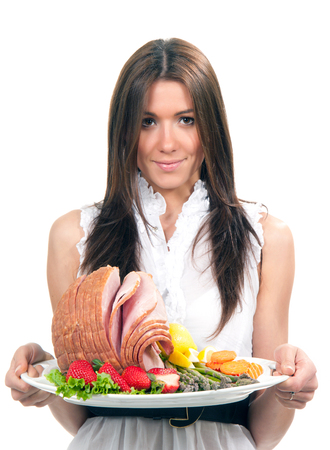 baked meat: Woman with plate delicious whole baked honey sliced ham meat strawberries vegetable salad carrots asparagus lemon for dinner isolated on a white background