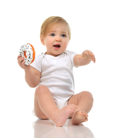 baby food: Infant child baby boy toddler playing on a floor with sweet donut fast food isolated a white background