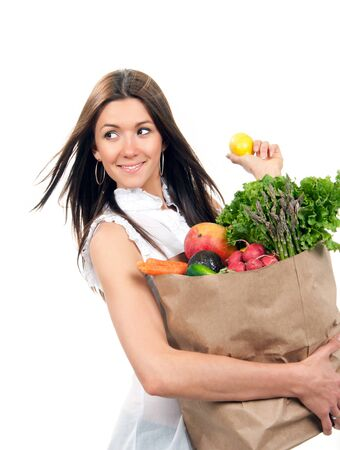 isolated woman: Happy young woman holding a shopping bag full of groceries fruits and vegetables holding lemon isolated on a white background