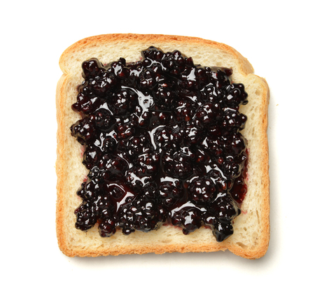 sandwich spread: Dark red raspberry preserves spread over a slice of white sandwich bread isolated on a white background