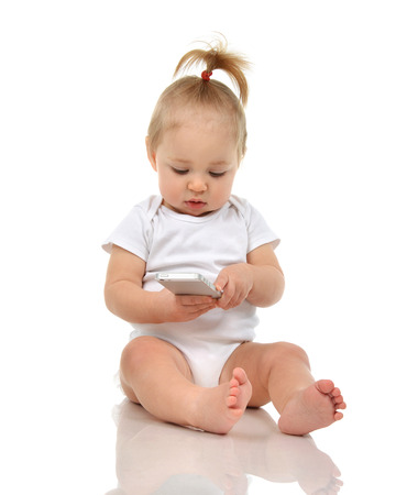 Happy infant child baby boy sitting smiling playing texting by mobile cellphone isolated on a white background Stock Photo