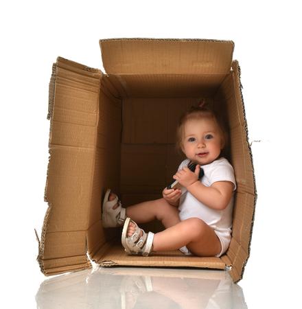 boite carton: Heureux petit bébé enfant fille se cachant dans une boîte en carton ayant du plaisir avec téléphone mobile isolé sur un fond blanc