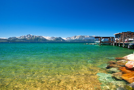 lake beach: Beautiful exotic beach for relax with snow mountains azure clear water lake on sand