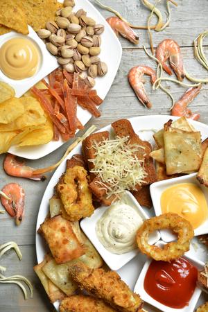 패스트 푸드 스낵 컴포지션과 텍스트 복사본 피스타치오 너트 말린 된 짠 생선 스트립 및 croutons 치즈와 함께 치킨 너 겟슨 소박한 나무 배경입니다. 건