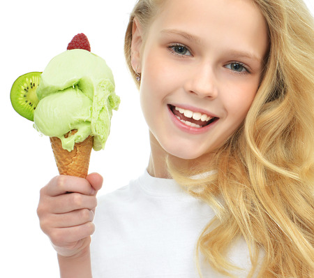 Pretty baby girl holding ice cream in waffles cone with raspberry and kiwi happy smiling isolated on a white background Stockfoto