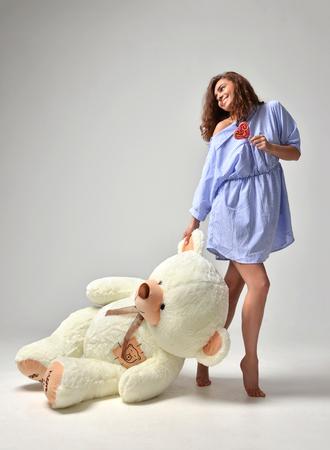 oso blanco: hermosa joven con gran oso de peluche de juguete de peluche sonriente feliz con estallido del polo rojo caramelo en el fondo gris