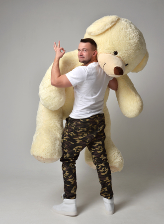 Man hold big teddy bear soft toy as a present to his girlfriend for birthday party on grey background Stock Photo