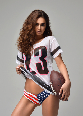 football jersey: Sexy happy Fierce young woman Football Player with ball standing smiling isolated on a white background