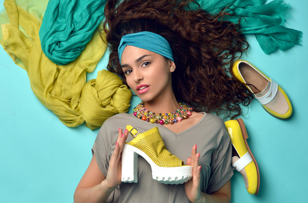 High fashion look glamour beautiful curly hair American woman with blue and yellow shoes and nails manicure on blue mint background