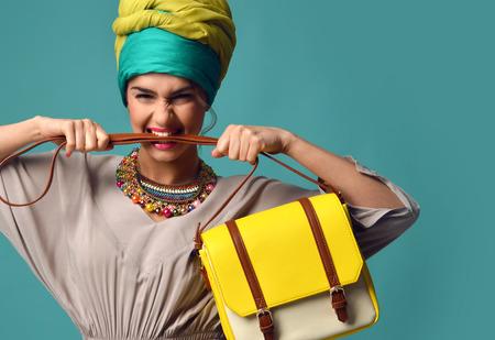 Vrouw schreeuwen schreeuwen en het eten van de riem van de hand te houden stijlvolle mode gele lederen handtas geïsoleerd op een blauwe achtergrond munt