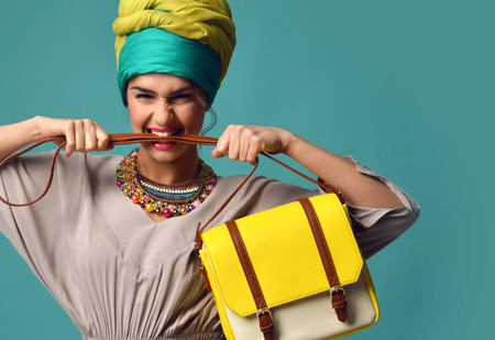 Woman yelling screaming and eating belt of hand hold stylish fashion yellow leather bag handbag isolated on blue mint background Reklamní fotografie - 59074276