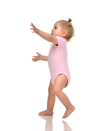 child hand: Infant child baby girl kid toddler in pink body cloth make first steps isolated on a white background