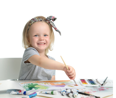 children painting: Happy cheerful baby girl child drawing with brush in album with painting tools laughing isolated on a white background