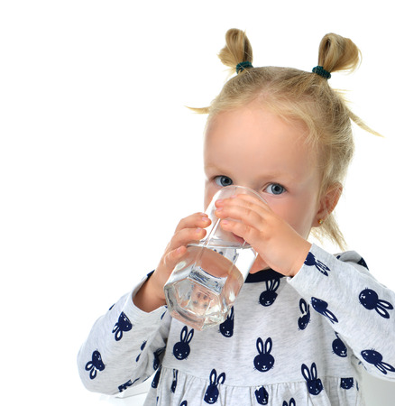 Child baby girl sitting with glass of drinking water isolated on white background