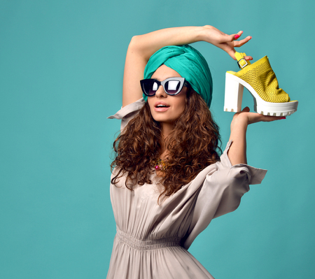 High fashion look glamour beautiful curly hair American woman in modern cat eyes sunglasses with white yellow shoe and nails manicure on blue mint background