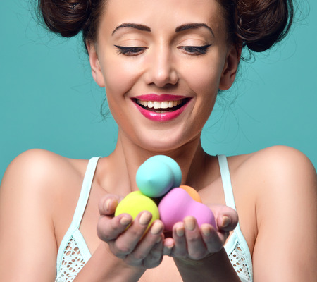 Happy surprised woman hold colorful sponge for applying foundation for make-up on face skin cares on blue mint background Archivio Fotografico
