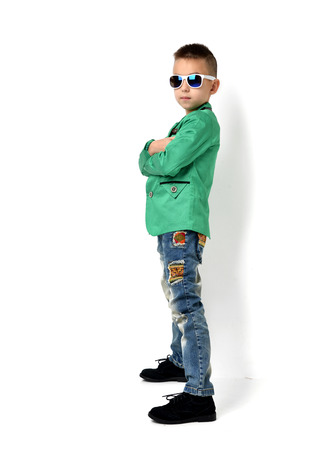 fashion boy: Fashion beautiful little boy in sunglasses blue cloth jeans standing and green jacket over white background
