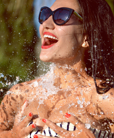 Young beautiful woman with water splashes in sunglasses and bikini laughing smiling on tropical resort and spa hotel Archivio Fotografico