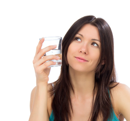 drink water: Young happy woman drink glass of drinking water and looking at the corner. Healthy weight loss concept on a white background