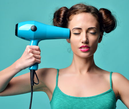 hair treatment: Happy young curly brunette woman with hair dryer on blue mint background. Hair style beauty concept