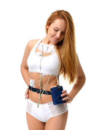 Woman wearing holter monitor device for daily monitoring of an electrocardiogram 24 hour Heart investigation activity isolated on a white background Stock Photo