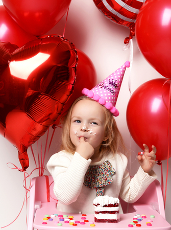 Little baby girl kid celebrate her third birthday with sweet cake on a light party background with red colorful balloons decorations