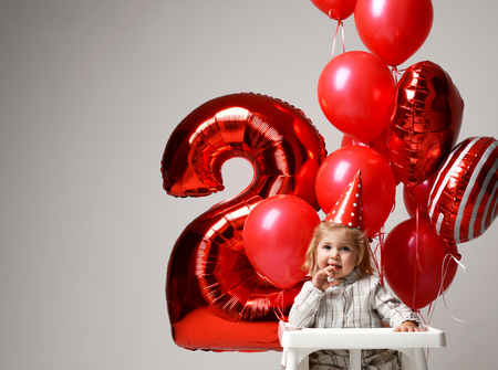 Little baby girl celebrate her second birthday with sweet cake on a light party background with red colorful balloons decorations Stock Photo