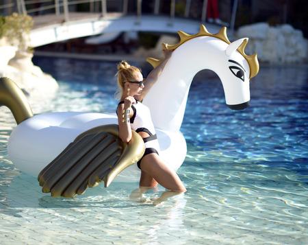 Jonge mooie mode vrouw ontspannen in luxe zwembad resorthotel met enorme grote eenhoorn drijvende pegasus Stockfoto