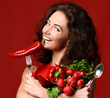 Pretty cheerful young woman posing with fresh red vegetables radish pepper green leaves lettuce parsley smiling. Dieting. Healthy eating concept on red background Stok Fotoğraf