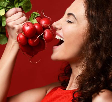 Close-up portret van jonge sport vrouw eten verse radijs groene bladeren. Dieet. Gezond eten concept op rode achtergrond