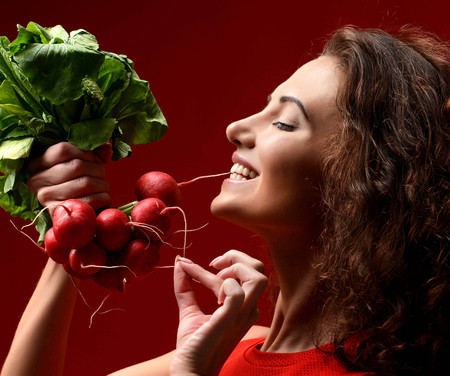 Pretty cheerful young sport woman posing with fresh radish green leaves. Dieting. Healthy eating concept on red background Stok Fotoğraf