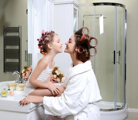 Joven madre e hija en rulos en un cuarto de baño feliz sonriente concepto de cuidado de la piel familiar en el baño