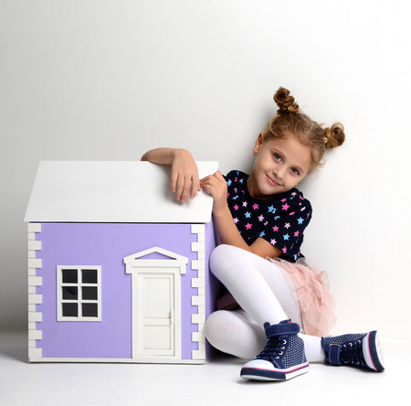 dollhouse: Baby Girl Kid playing with big purple house in play room at home or kindergarten on gray background Stock Photo