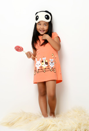 Happy young little child girl standing with sweet lollypop surprised looking at the corner on white background