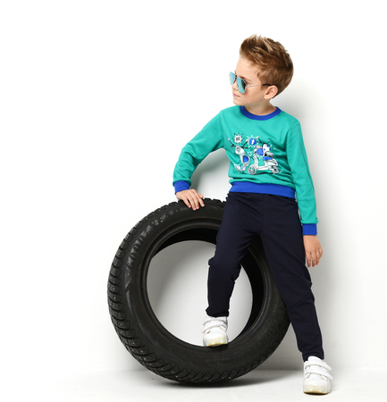 Happy young boy sitting in blue green sweater on a tyre wheel thinking and looking at the corner positive attitude on white background