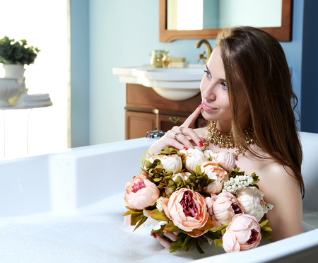 Luxury fashion brunette woman in hotel spa lying in bath tub with bouquet of flowers looking at the corner Stock Photo